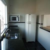Cozinha com microondas e geladeira.
