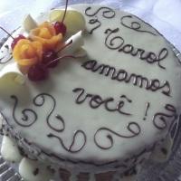 Bolo aberto coberto com chocolate branco e dedicatória com chocolate ao leite, decorado com rosas de