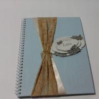 Álbum com capa rígida revestido com tecido, miolo em papel reciclato e acabamento wire-o.