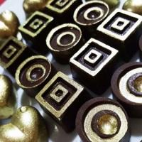 Bombons de Chocolate ao Leite ou Meio Amargo, recheados e decorados com pó comestível dourado.