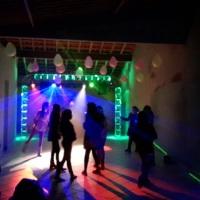 Festa com iluminação e som, estrutura em trave com efeito neon