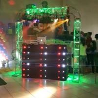 Estrutura com som, luz e mesa de dj decorada com cortina de led