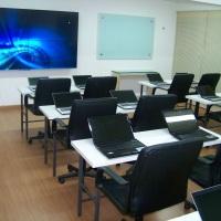 Auditório 1 com mesas e notebooks