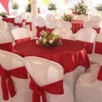 Mesa com tampo redondo e toalha longa branca com cobre mancha vermelho e cadeiras com capas brancas.