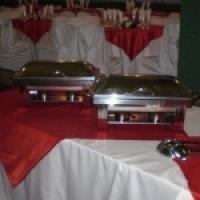 Pranchão com toalha longa branca e cobre mancha vermelho e dois rechaud de 9 litros cada.