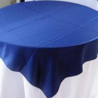 Mesa com tampo redondo com toalha longa branca e cobre mancha azul marinho.