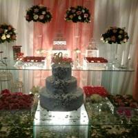 decoração mesa de vidro com arranjos, bolo cenográfico e doces finos
