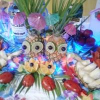 Mesa decorada com esculturas em frutas e e luzes.