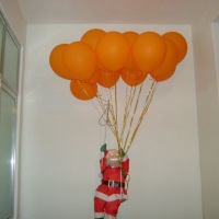 Papai Noel com balões de gás hélio.