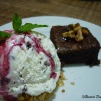 Sobremesa brownie de chocolate com nozes e sorvete de flocos com calda de frutas vermelhas...